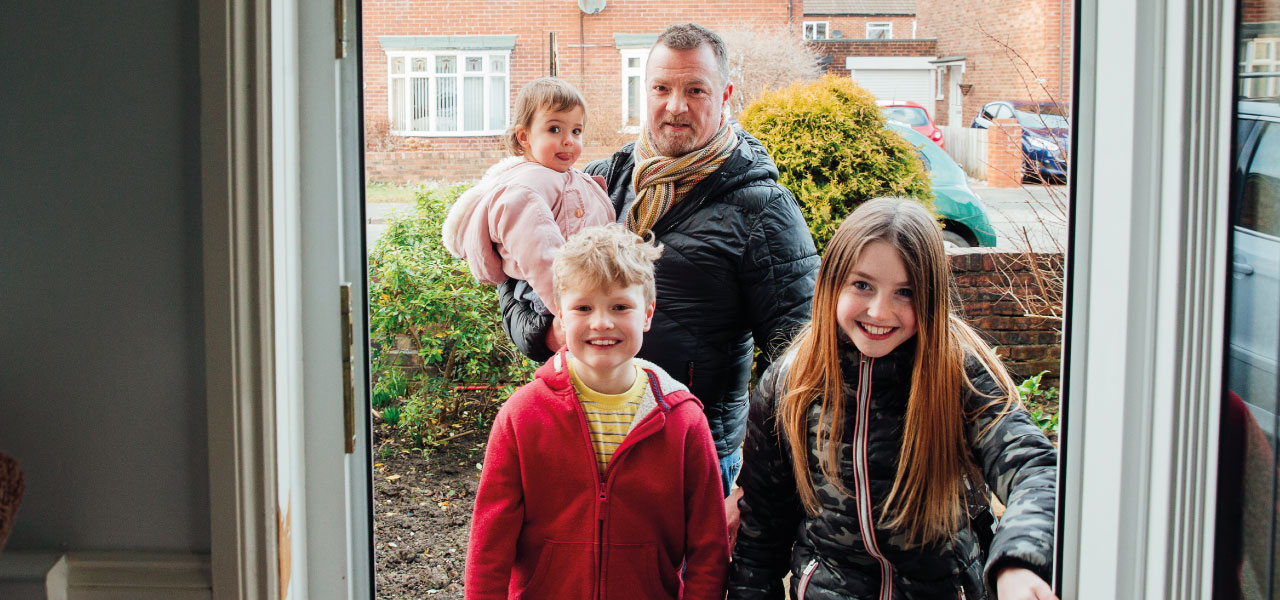 A family walking in the front door of their house