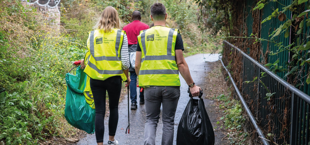 Two people walking in high-vis jackets with litterpicking gear