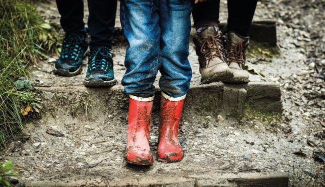 A child's feet wearing red wellies